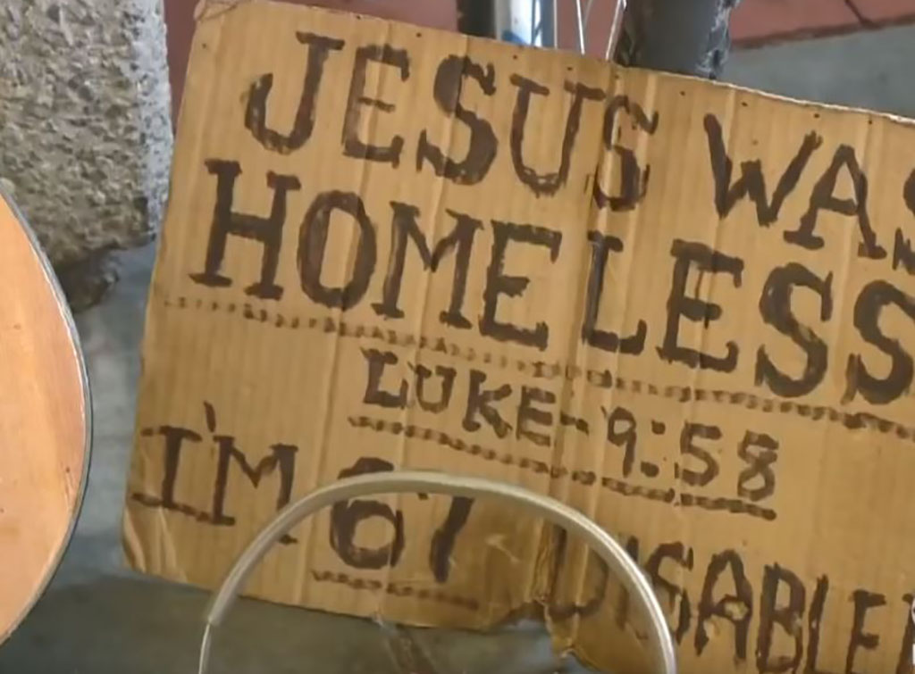 a cardboard sign with a message about Jesus