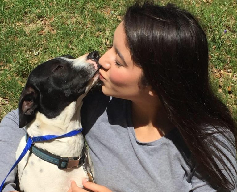 woman kissing dog