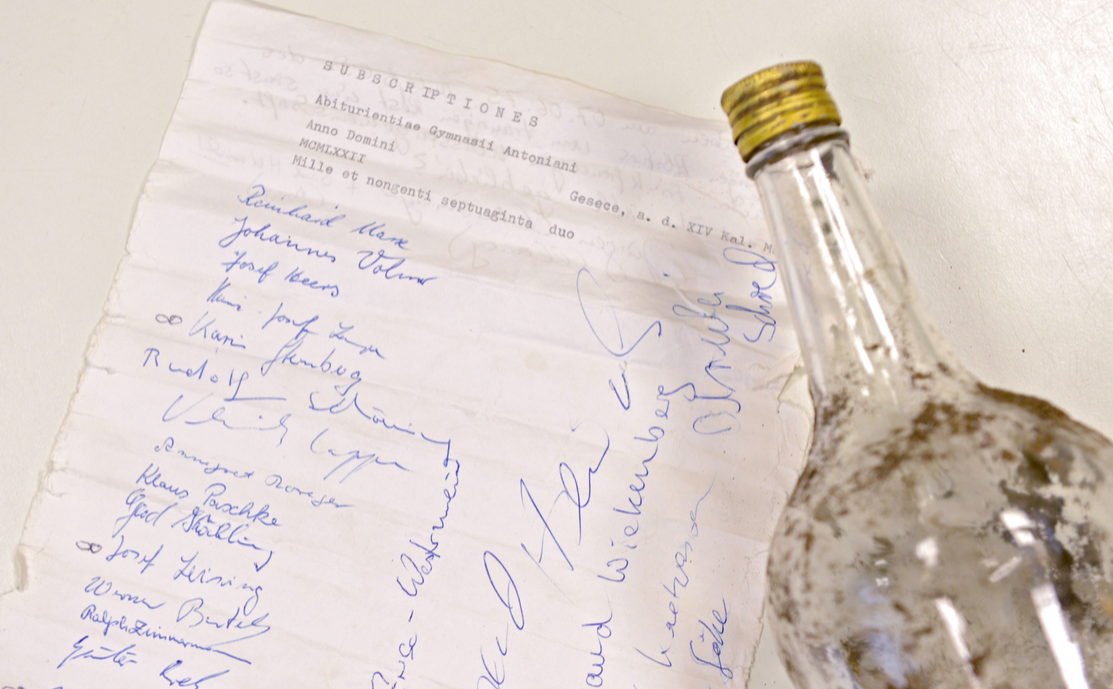 An old and dirty bottle with its contained message are presented on a table in Geseke, Germany