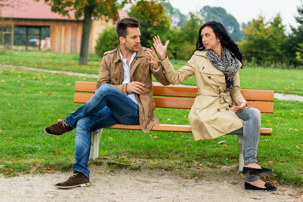 man and woman sitting on a bench in an argument