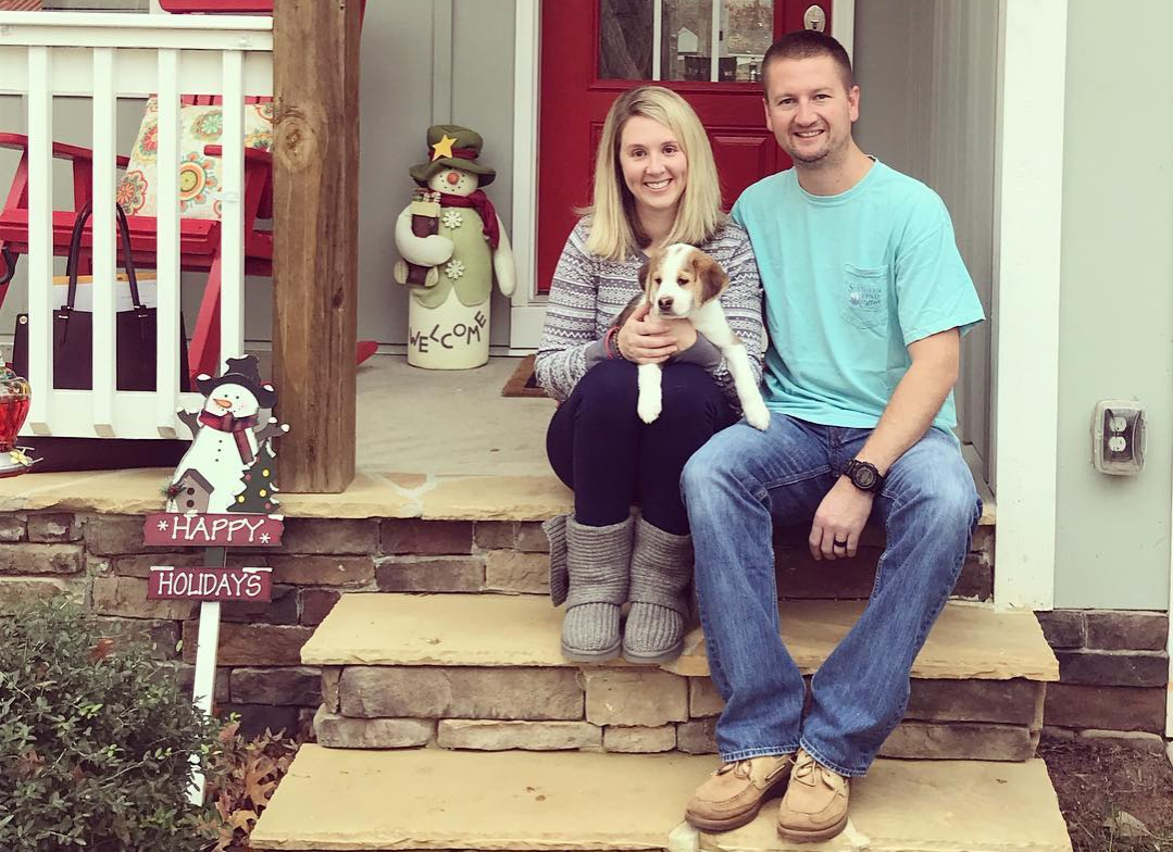 John and Katie Black with a puppy on the steps of their house