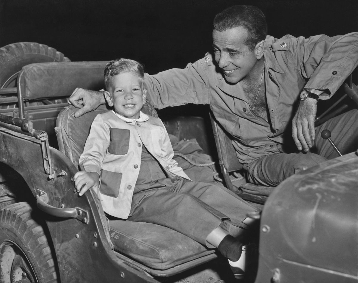 American actor Humphrey Bogart (with his son Stephen in a jeep on the set of the 1953 film 'Battle Circus'