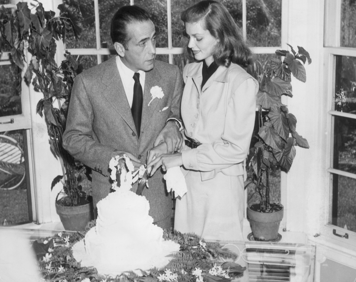 American actors Lauren Bacall and Humphrey Bogart cut the cake at their wedding.