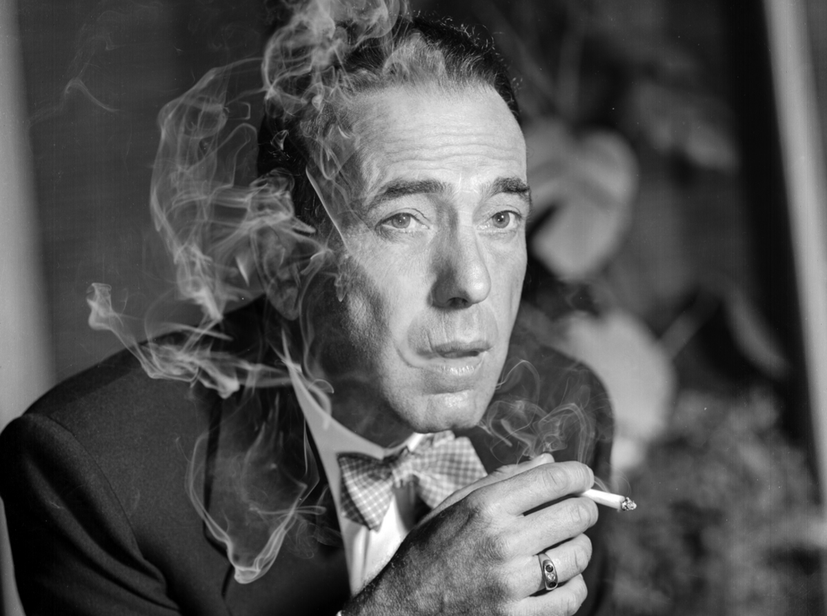 Headshot of actor Humphrey Bogart, wearing a bow tie and smoking a cigarette