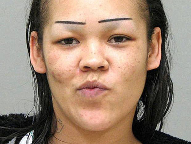 a mugshot of a woman with straight eyebrows
