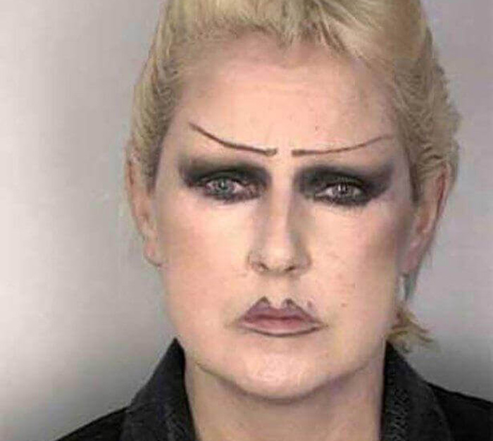 mugshot of a woman with sad eyebrows