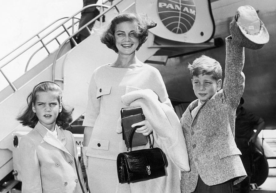 bacall and children in front of a plane
