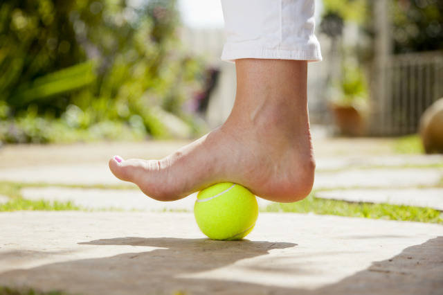 a foot on top of a tennis ball