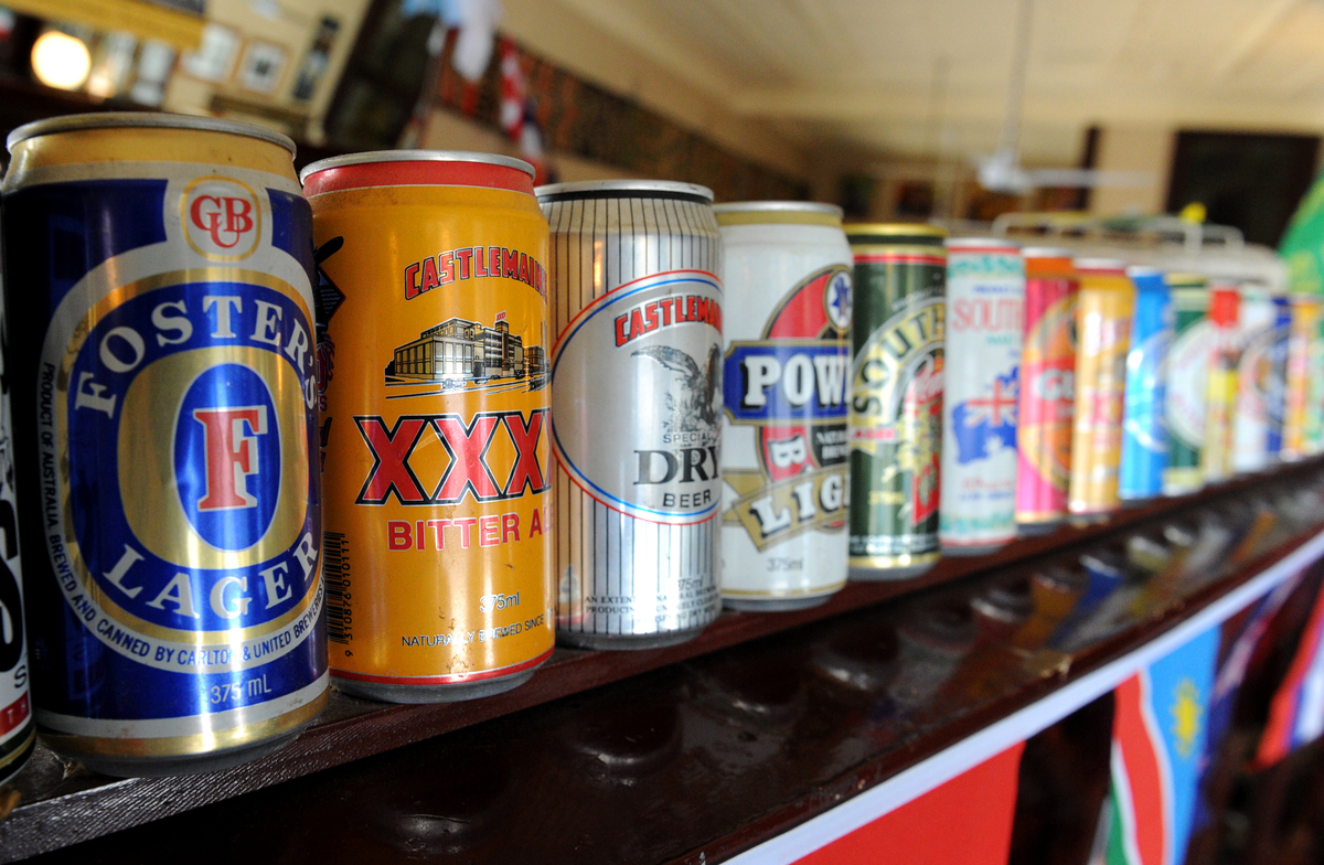 An empty can of Foster's Lager  adorns the wall next to cans of other beers