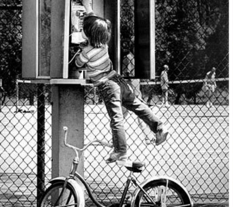 kid hanging from telephone