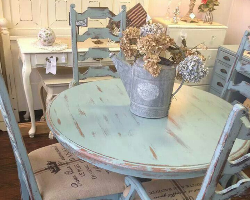 distressed blue table with a tin watering can with fake flowers in it