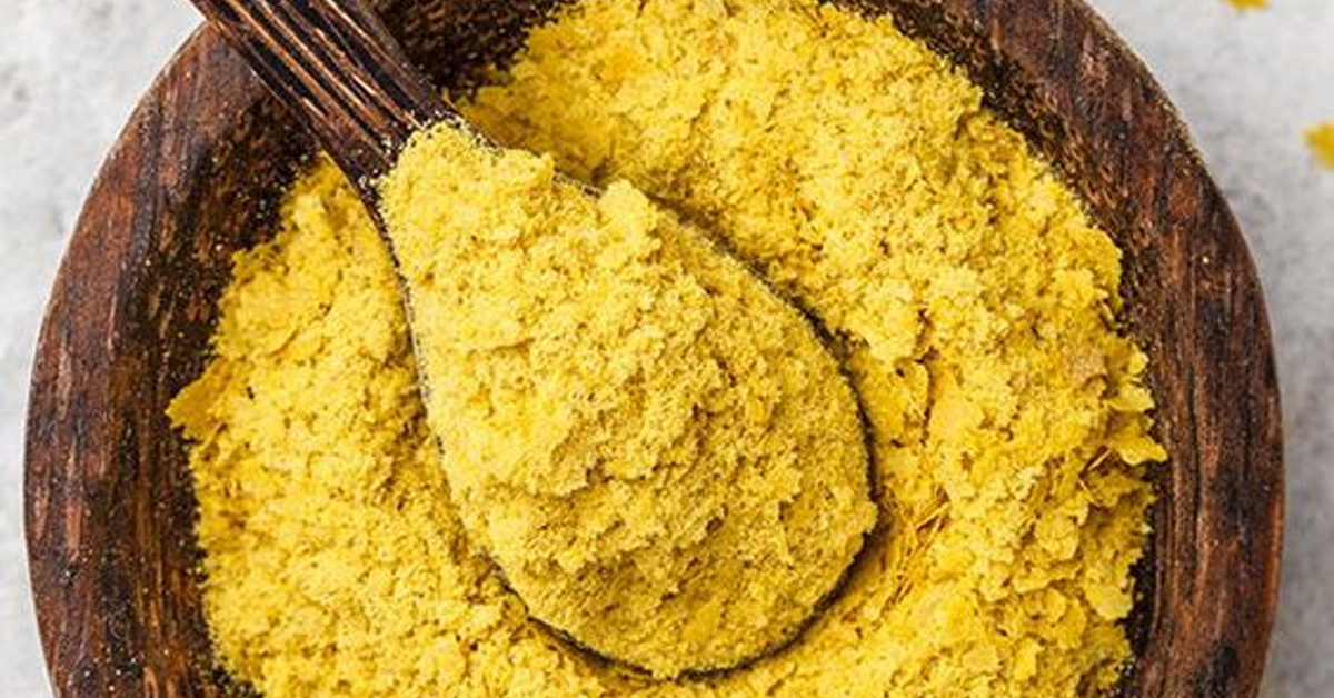 nutritional yeast inside a wooden bowl with a spoon