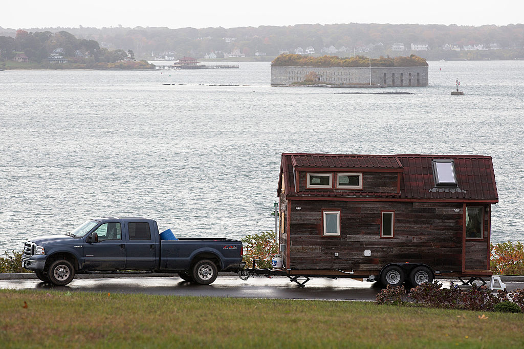 truck trailing tiny home behind it