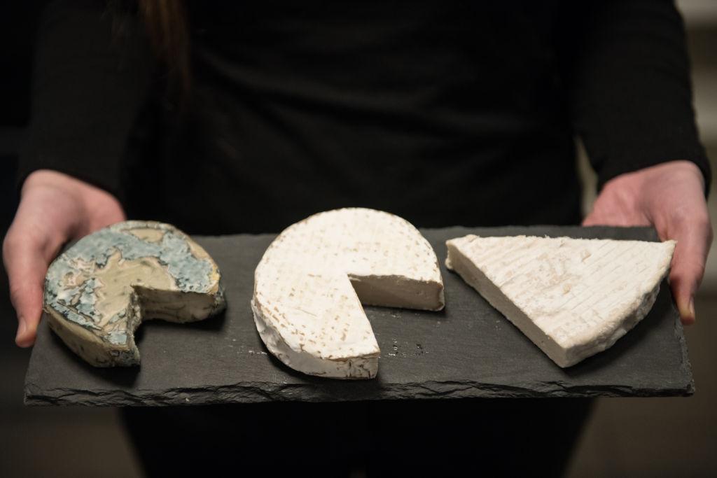 three vegan cheese varieties on a plank