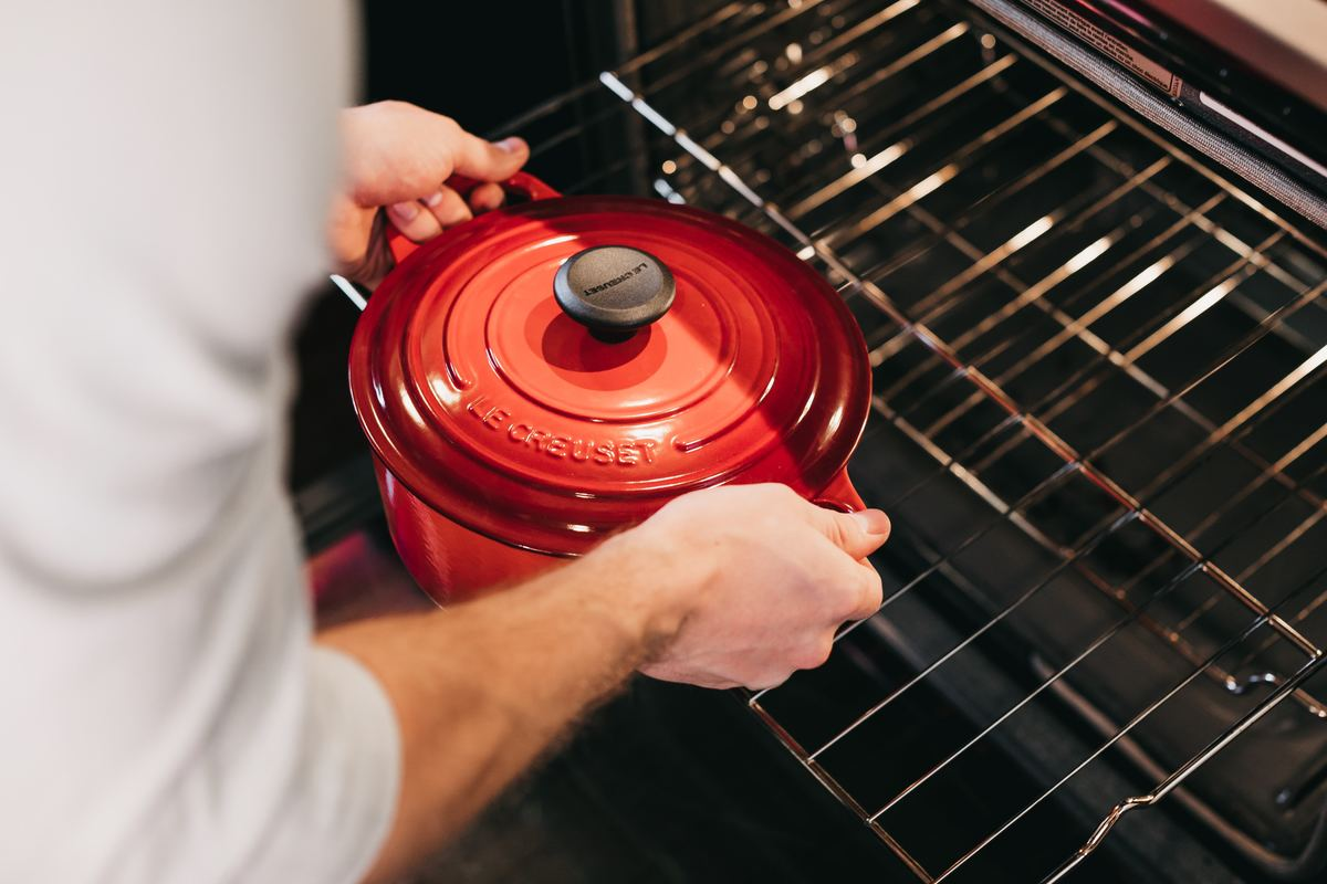 Man places red pot inside of oven