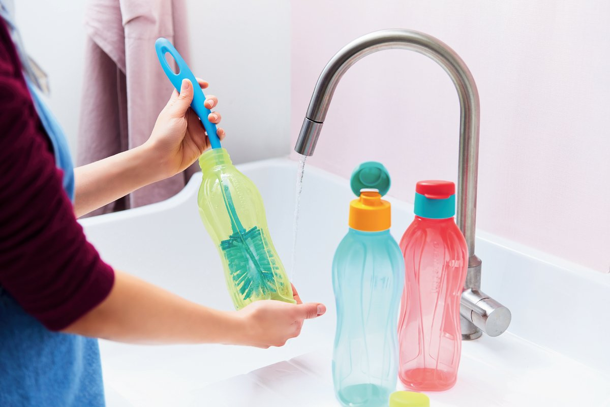 Woman cleans tupperware bottles with an Eco Bottle Brush