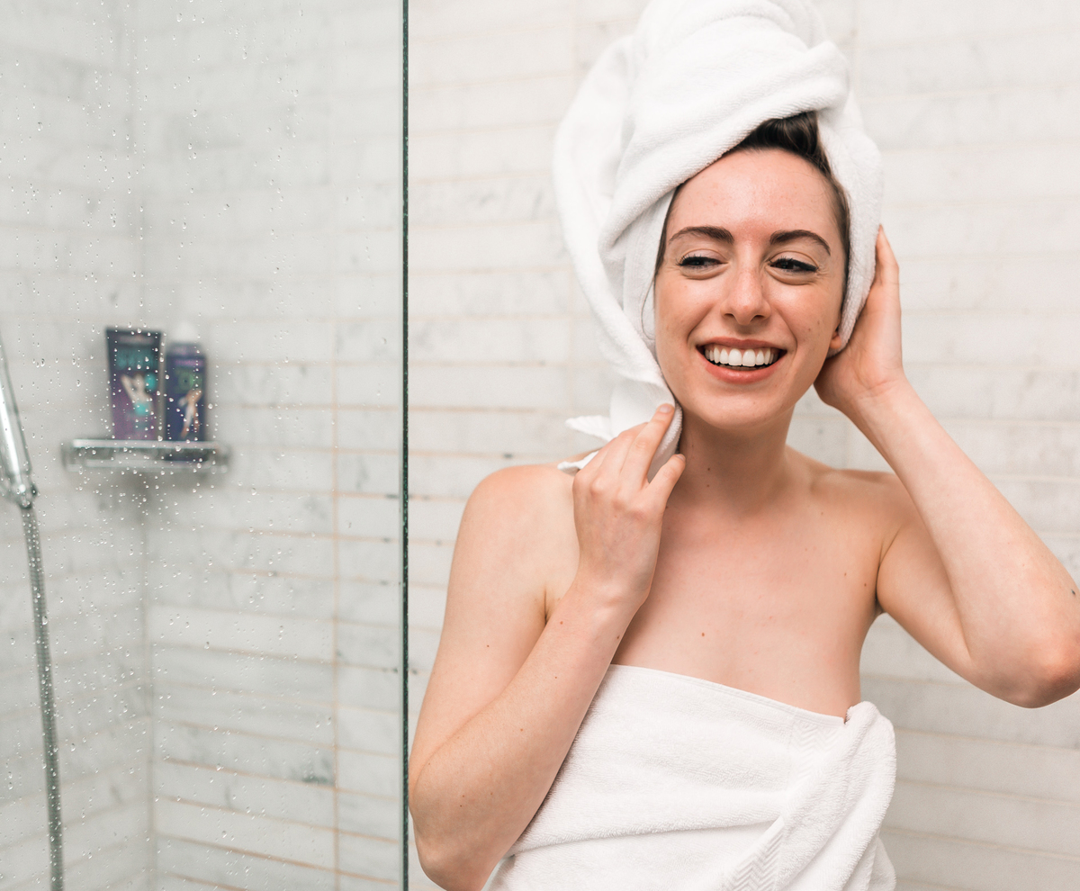 Woman wears white towels upon leaving the shower