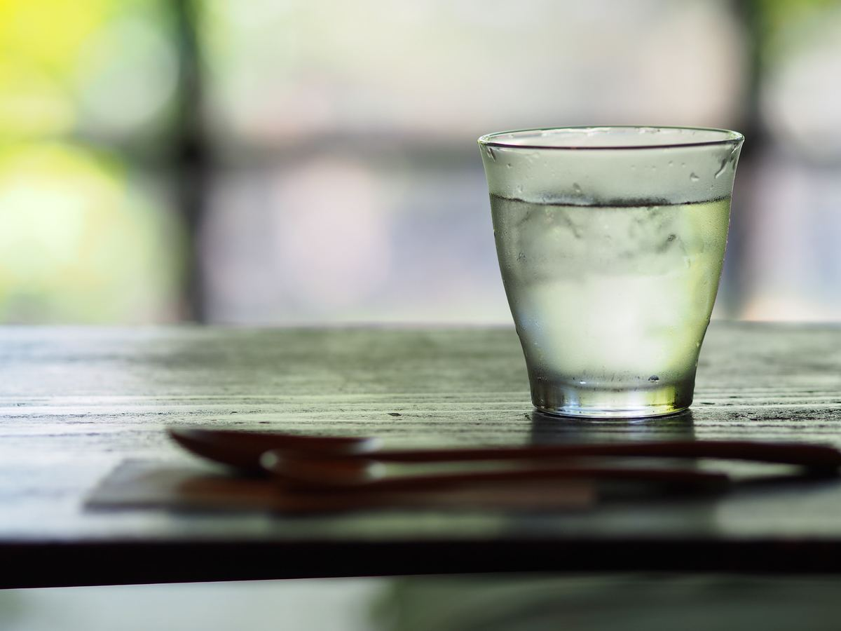 Small glass of cold water with a spoon in front