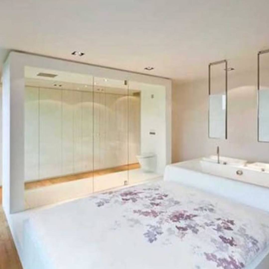 open concept bedroom with glass wall looking into bathroom