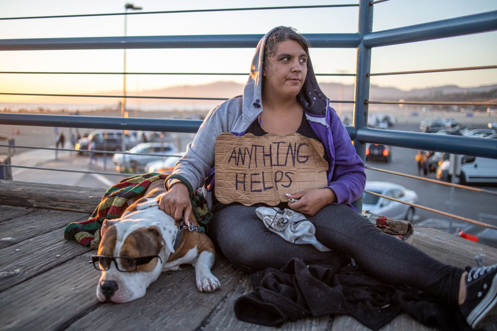A homeless woman holds a sign that reads