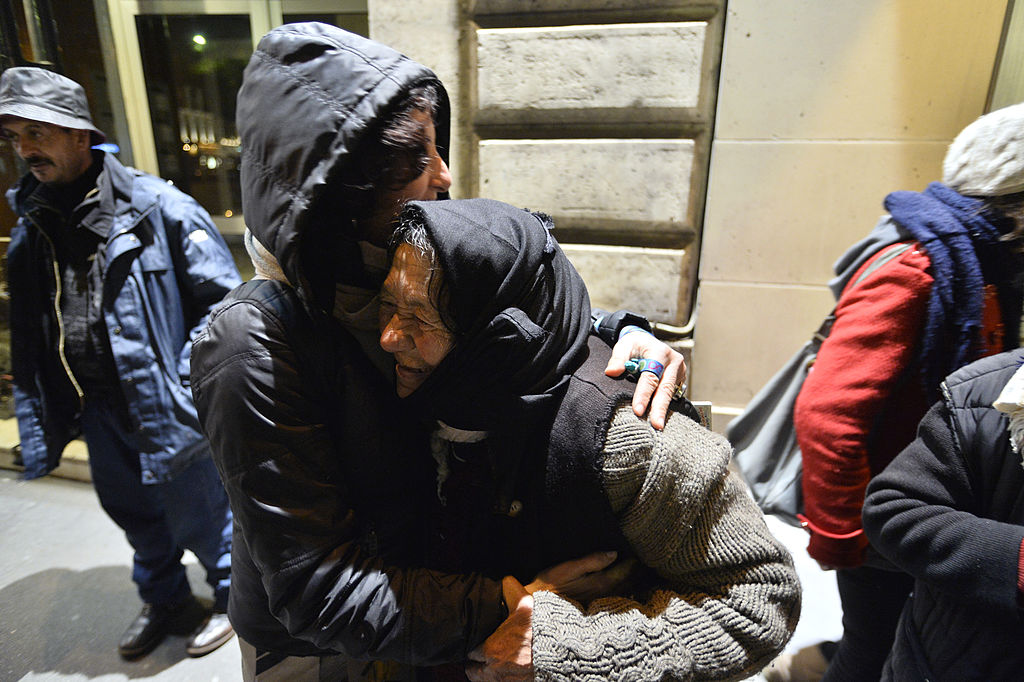 A homeless woman smiles while being embraced by a woman on the sidewalk.