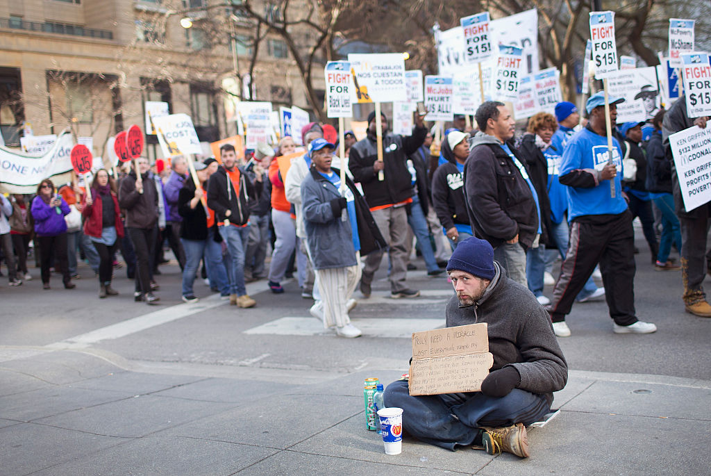 A homeless man sits on the ground in front of a protest to increase the minimum wage.