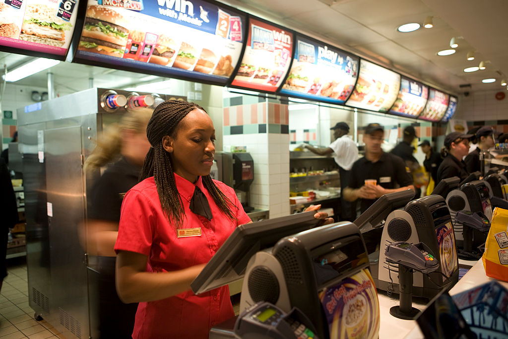 A woman stands behind the cash register at a McDonald's.