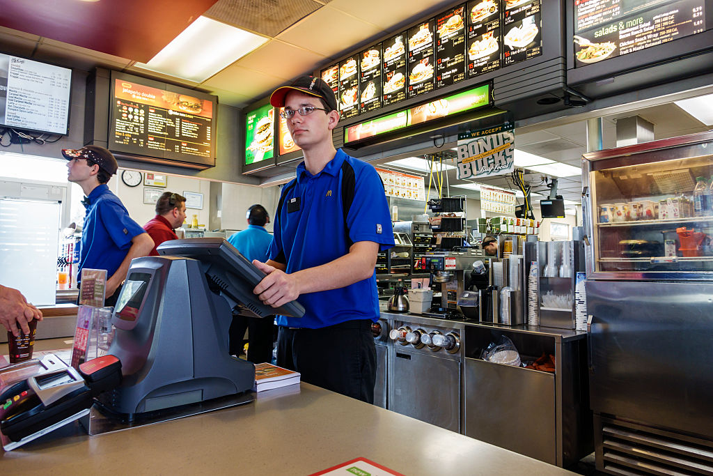 A young man stands at the cash-register of a McDonald's.
