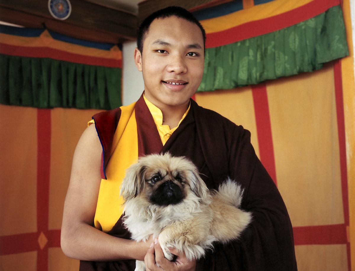 Monk holds his pekinese dog Dekyi