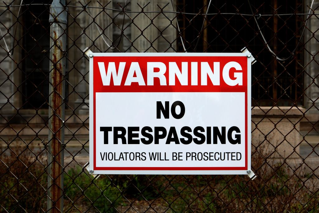 A no trespassing sign hangs on a metal gate.