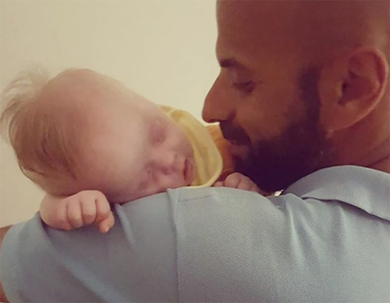 Newborn Alba sleeps on Luca's shoulder.