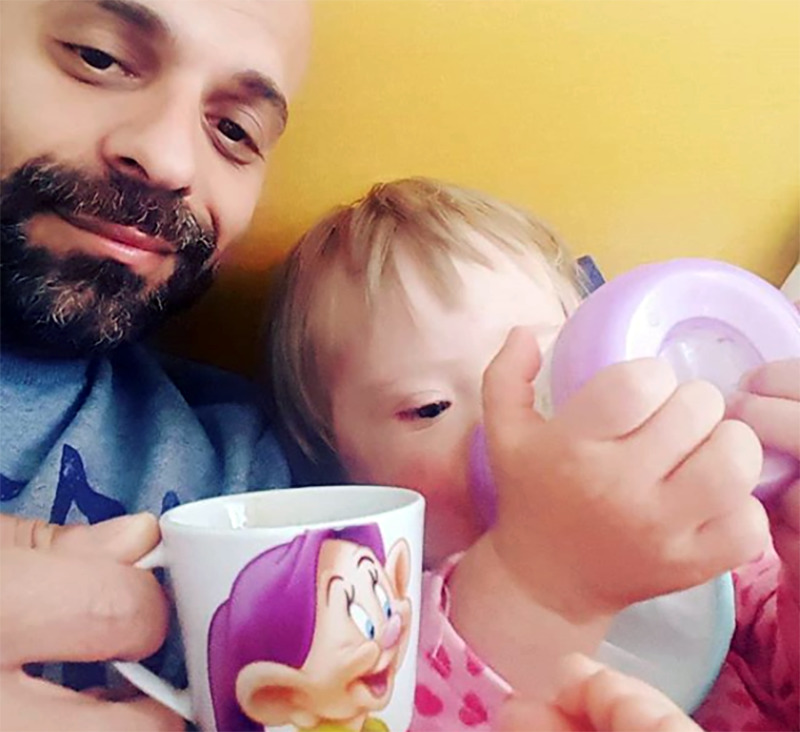 Luca holds up a Snow White mug while Alba drinks from a sippy cup.