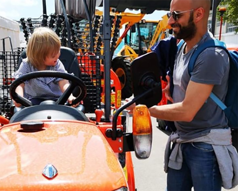 Alba pretends to steer a tractor