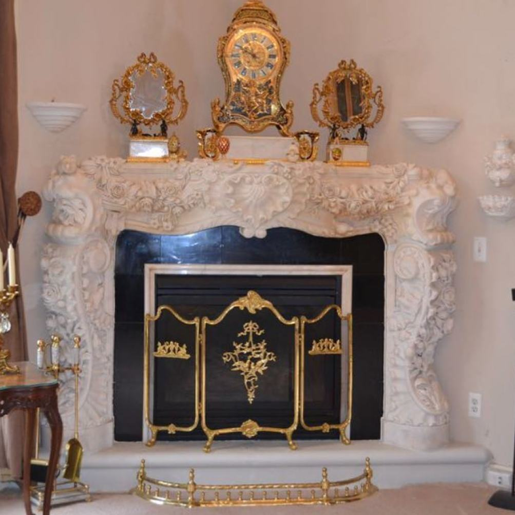 white fireplace with intricate carvings and gold decor