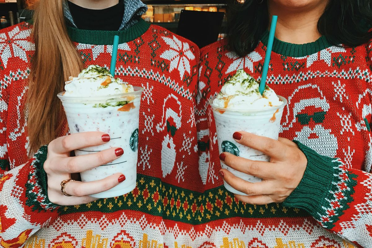 fans holding a fruitcake frappuccino