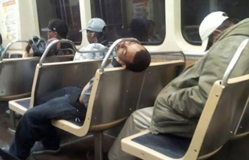 Man sleeping with head under bar