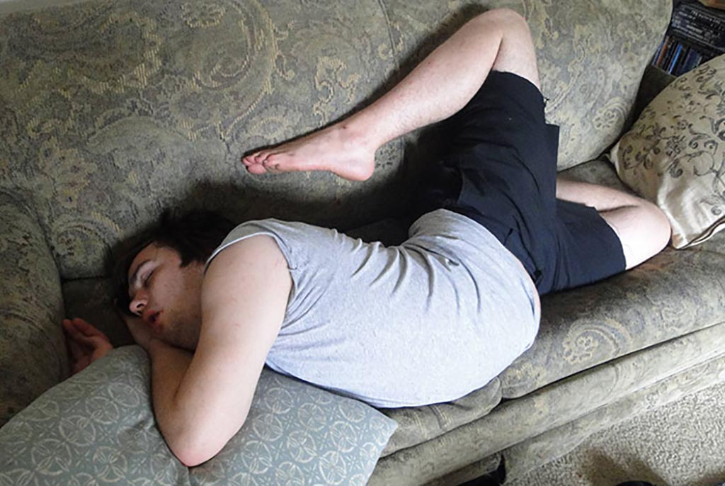 Guy sleeping like cupid