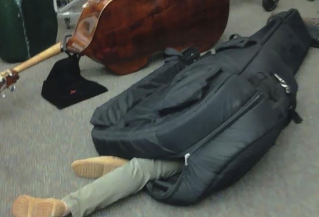 Musician sleeping in their bass case