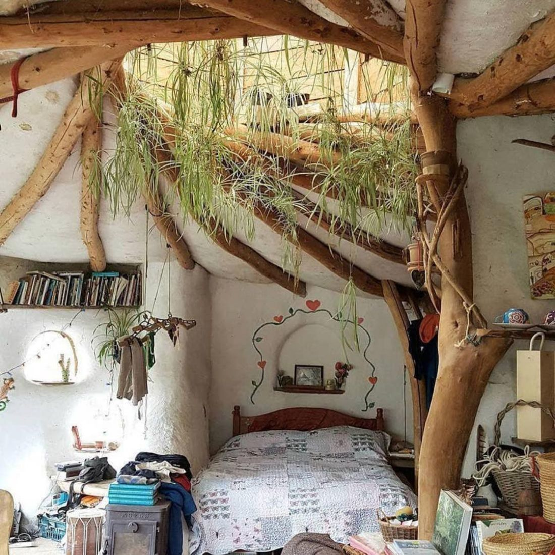 bedroom with wooden beams and skylight covered in plants