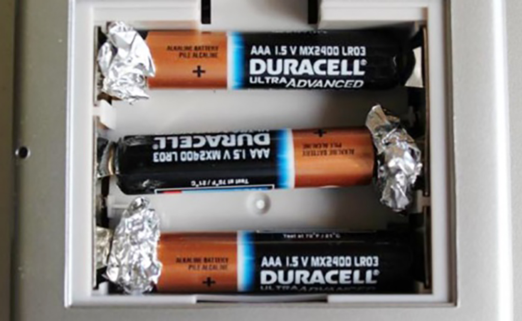 Aluminum foil pressed against battery