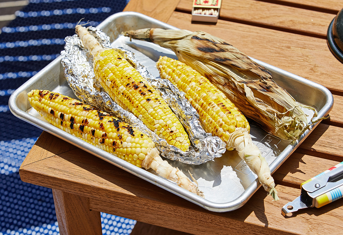 Grilled corn on the cob rests on a pan outdoors.