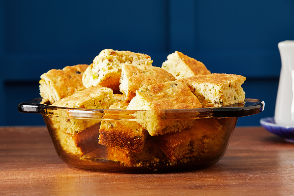Cornbread slices fill a bowl in front of a blue backdrop.