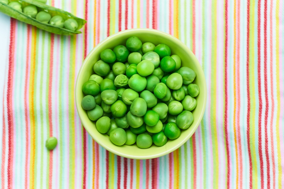 A bowl on a striped tablecloth holds peas.