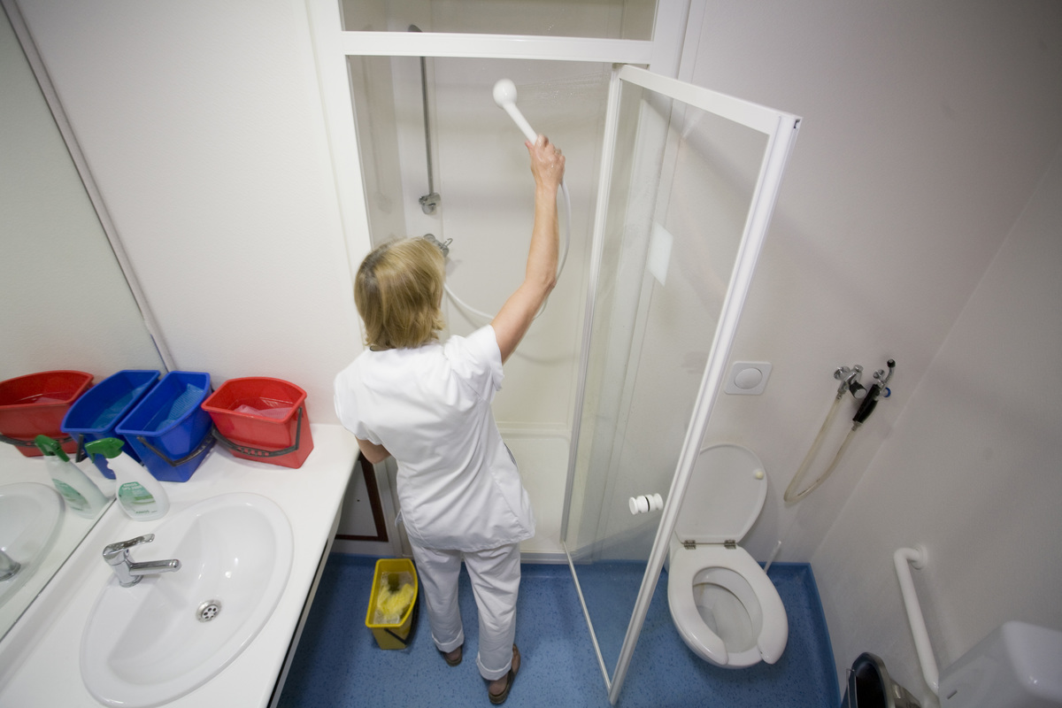 A worker cleans the shower at the Maternity of Saint Vincent De Paul Hospital.