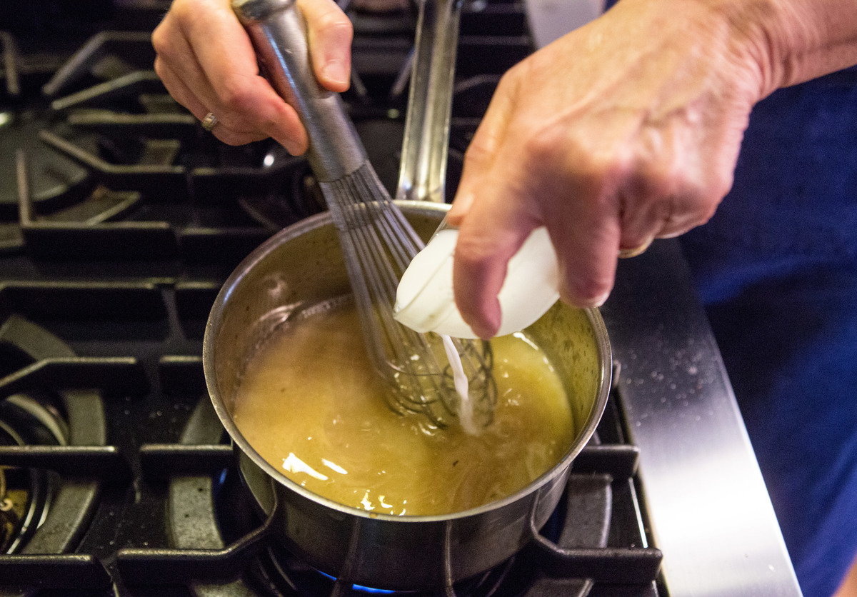Food editor Sheryl Julian whisks cornstarch diluted with water while making gravy.