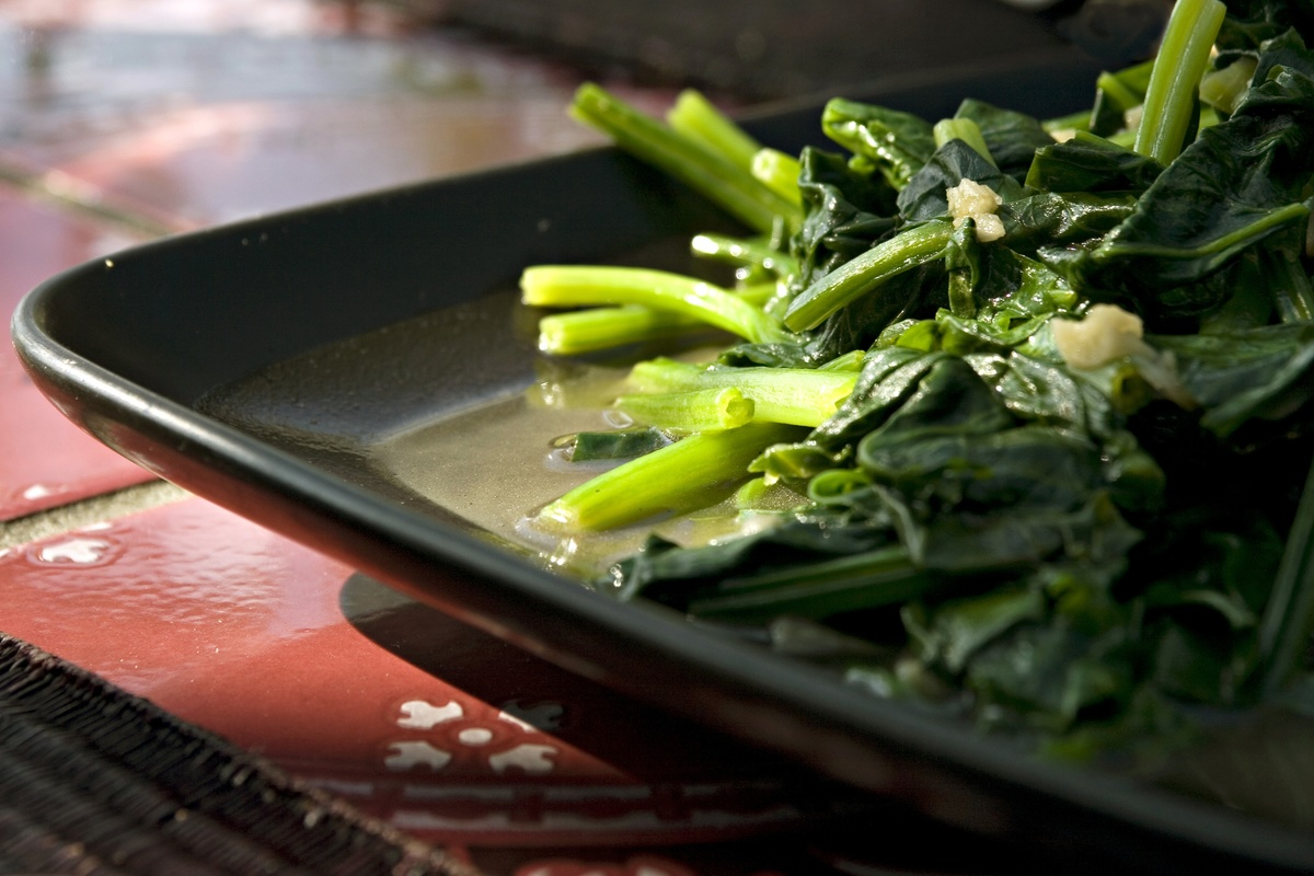 Freshly cooked chinese spinach sits on a pan.