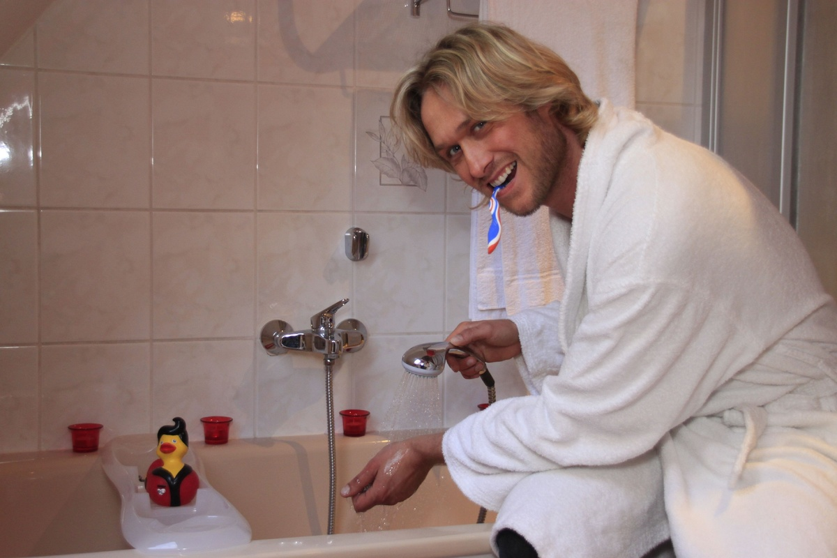 A man kneels near his running bathtub while brushing his teeth.
