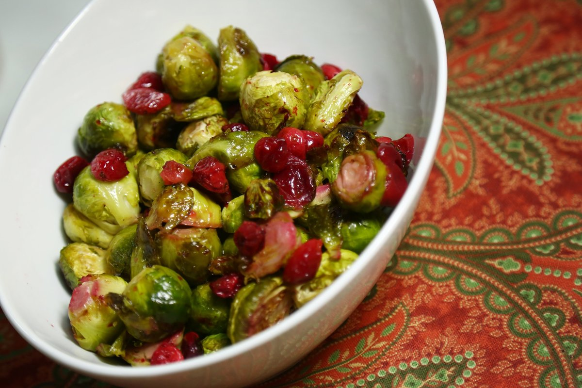 Roasted Brussels sprouts and cranberries are in a white bowl.