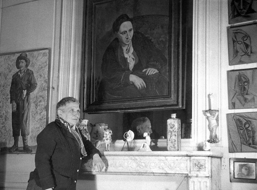 Gertrude Stein poses beneath a portrait of herself.