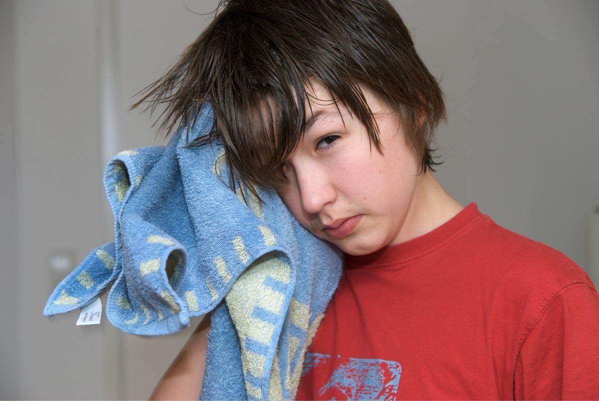 A boy dries his hair with a towel.